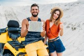 Fényképek happy young couple with atv showing digital tablet with map on screen and thumb up at desert