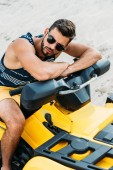handsome young man on all-terrain vehicle in desert