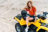 Fotografia vista di alto angolo di giovane donna felice che si siede sul veicolo all - terrain sulla sabbia