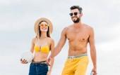 Fotografia bella giovane coppia in abiti da spiaggia con la sfera di pallavolo davanti al cielo nuvoloso