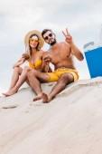 Fotografie pohled zdola mladý pár s kokosovým koktejly sedí na písku před zamračená obloha a ukazuje míru gesto