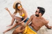 vysoký úhel pohled mladého páru s kokosovým koktejly na písku