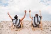 fiatal pár, kókusz koktélok lazíthat a napozóágyak, a homokos dune hátsó nézet