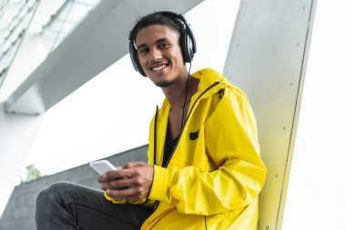 smiling mixed race man in headphones listening music with smartphone and looking at camera at city street