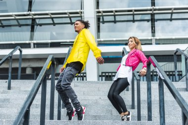 low angle view of young multiethnic couple dancing on stairs at urban street