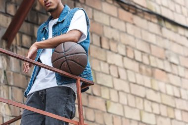 cropped image of young stylish man standing with basketball ball at street