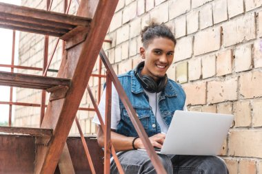 smiling mixed race male freelancer in headphones working with laptop at street