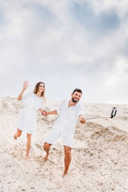 Playful young couple taking selfie with monopod and smartphone in desert stock vector