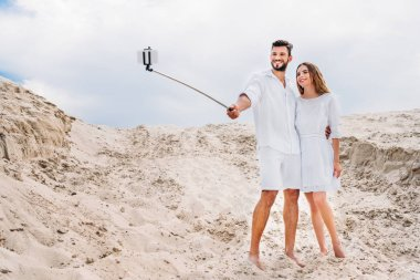 Beautiful young couple in white clothes taking selfie with monopod and smartphone in desert stock vector