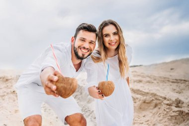 happy young couple in white with coconut cocktails looking at camera