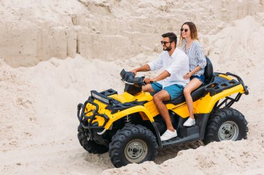 beautiful young couple riding yellow all-terrain vehicle in desert