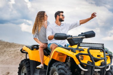 Active young couple taking selfie while sitting on ATV in desert stock vector