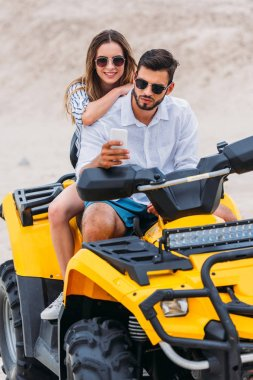 beautiful young couple taking selfie while sitting on ATV in desert