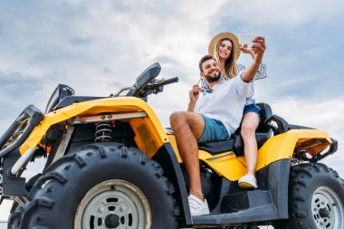Happy young couple sitting on ATV and taking selfie stock vector