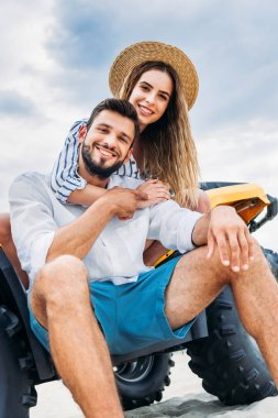 bottom view of happy young couple sitting on ATV in front of cloudy sky