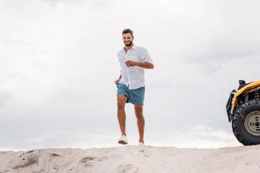 attractive young man running on sand dune in front of cloudy sky