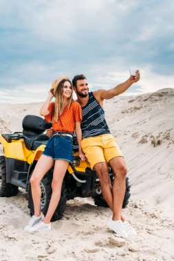 Smiling young couple with ATV taking selfie in desert stock vector