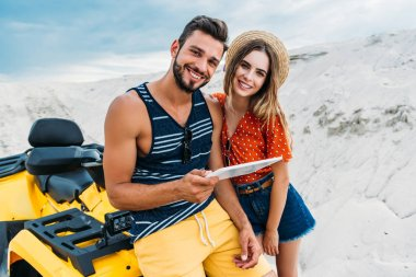 happy young couple with ATV using digital tablet in desert and looking at camera