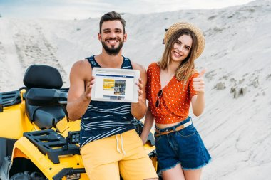 beautiful young couple with atv showing digital tablet with booking website on screen and thumb up at desert