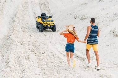 rear view of young couple going to ATV by sandy dune