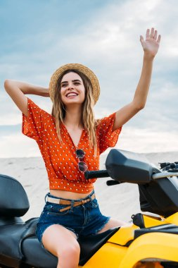 smiling young woman sitting on all-terrain vehicle in desert waving hand