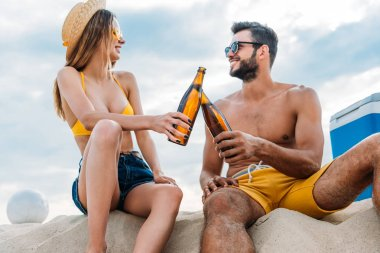 beautiful young couple clinking with bottles of beer while sitting on sand