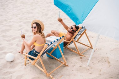 high angle view of happy young couple with coconut cocktails relaxing in sun loungers on sandy beach
