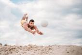 Fotografia giovane bello salto per palla giocando a beach volley