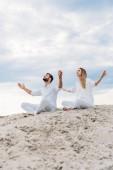 Fotografie young fit couple on yogi meditating while sitting on sandy dune in lotus pose (padmasana)