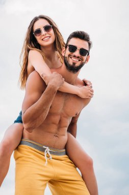 happy young woman piggybacking on boyfriends back in front of cloudy sky