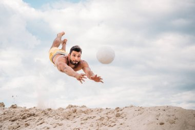handsome young man jumping for ball while playing beach volleyball