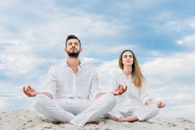 calm young couple meditating while sitting on sandy dune in lotus pose (padmasana)