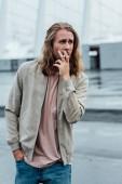 vonzó fiatal férfi cigaretta a dohányzás a felhős nap utca