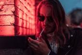 Fotografie hübscher junger Mann mit Sonnenbrille und Leder Jacke qualmender Zigarette unter Rotlicht auf Straße