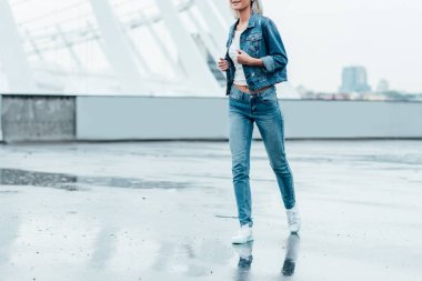 cropped shot of young woman in denim jacket and jeans running by street