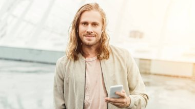 happy young man listening music with earphones and smartphone on street and looking at camera