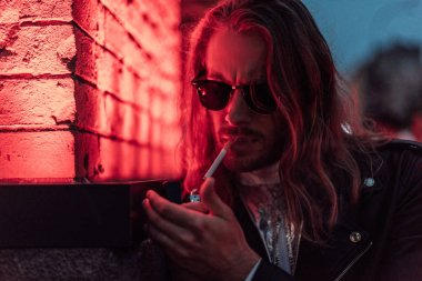 handsome young man in sunglasses and leather jacket smoking cigarette under red light on street