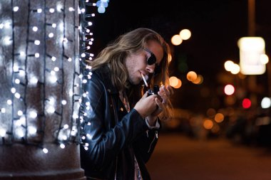 handsome young man in sunglasses and leather jacket smoking cigarette under garland on city street at night