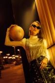 Fotografie pohled zdola atraktivní ženy v sluneční brýle s zlatý lesklý basketbalový míč na ulici v noci pod žlutým světlem