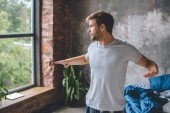 Fotografia fuoco selettivo del giovane che fa esercizio fisico durante il tempo di mattina a casa