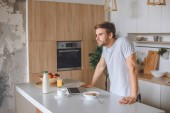 happy young man standing at table with breakfast and laptop at kitchen