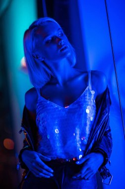 beautiful young woman in glossy tank top on street at night under blue light