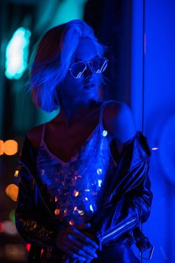 beautiful young woman in glossy tank top and sunglasses on street at night under blue light