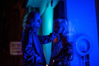 young stylish couple flirting under blue light on night street