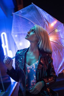 attractive young woman with umbrella looking up on street at night under blue light