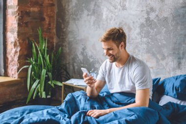 Smiling young man checking smartphone in bed at home stock vector