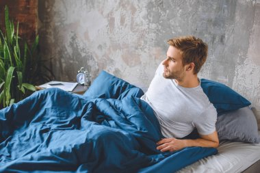 confident young man waking up in his bed during morning time at home