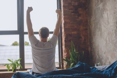 rear view of young man sitting on bed with raised arms during morning time at home