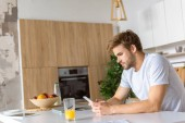 Photo serious young man using smartphone at kitchen table with juice and laptop