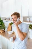 usmíval se mladý muž s kávou mluví na smartphone během ranní čas v kuchyni